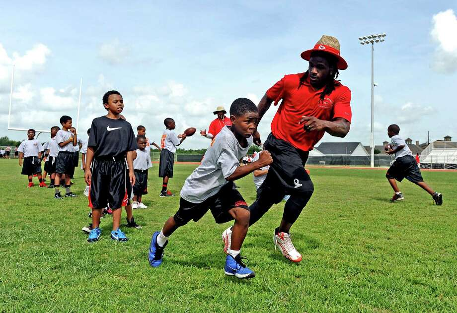 Jamaal Charles, right, of the Kansas City Chiefs, encourages the smaller kids as they warm up doing different running drills during the first day of the Jamaal Charles' football camp, held at Port Arthur Memorial High School on Friday, June 21, 2013. Photo taken: Randy Edwards/The Enterprise