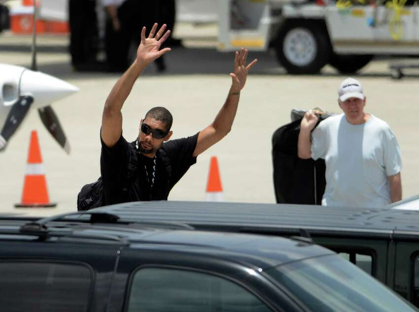 Tim Duncan waves before getting into his car after the San Antonio Spurs team members arrived at San Antonio International Airport on Friday, June 21, 2013, after representing the NBA's Western Conference in the Championship Series. They lost to the Miami Heat. Head coach Gregg Popovich is at right.