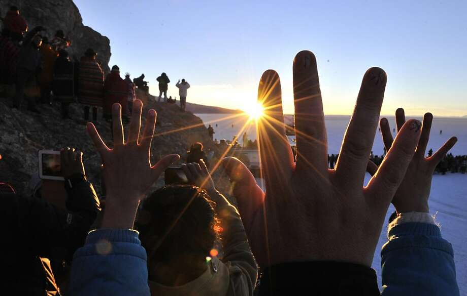 People raise their hands during a ritual at sunrise to celebrate the Aymara New Year on June 21, 2013 at the Uyuni salt flat in Bolivia. A crowd gathered to receive the first rays of Tata Inti (god Sun) during the celebration of the winter solstice that marks the beginning of the 5521st year in the Aymara calendar. AFP/PHOTO/Aizar RALDESAIZAR RALDES/AFP/Getty Images Photo: Aizar Raldes, AFP/Getty Images