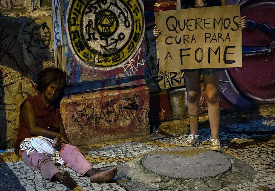"'Tropical Spring':A protester holding a placard that reads ""We want a cure for hunger"" stands by a homeless woman in Recife, Brazil. The nationwide demonstrations against  corruption and price hikes are now being called ""Tropical Spring."" Photo: Yasuyoshi Chiba, AFP/Getty Images"