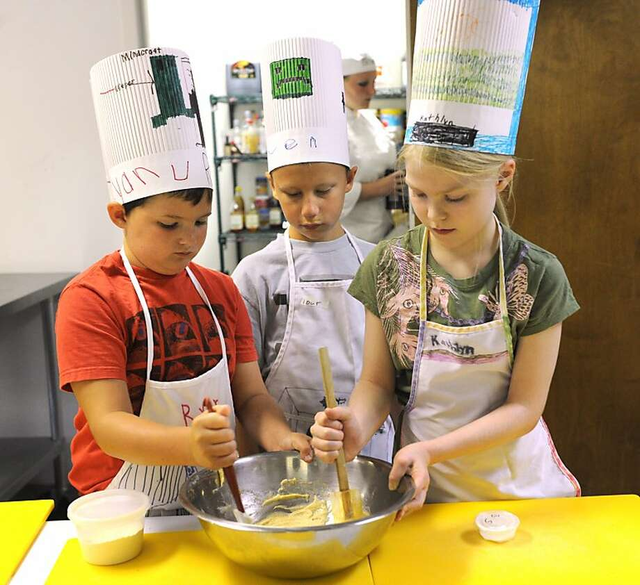 Too many cooks spoil the broth,but bakers Ryan Turner, Owen Pearsall and Kathlyn Tankersley seem to have the cookie dough under control at Culinary Camp in Abilene, Texas. Photo: Nellie Doneva, Associated Press