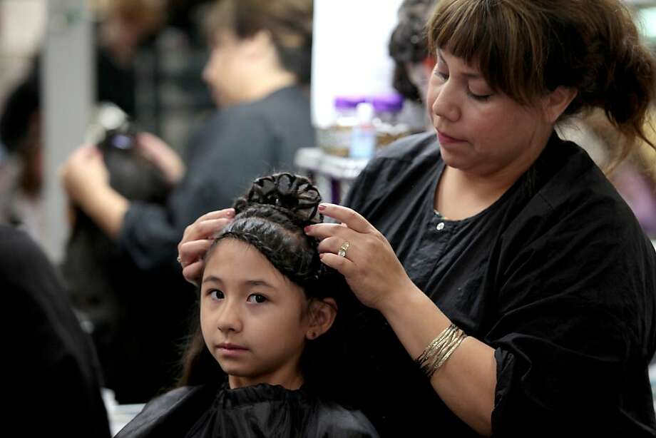 Hair to the throne: Alma Gamboa turns 7-year-old Julianna Ensies' locks into a tiara at a summer Princess Camp run by the Odessa College Cosmetology Department in Odessa, Texas. Photo: Ryan Evon, Associated Press