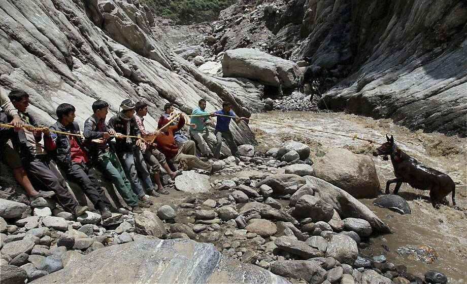 Long rope to the rescue:With a great tug, villagers free a horse that had become trapped in the current of the monsoon-flooded Mandakini River at Gauri Kund, India's Uttarakhand state. Photo: Uncredited, Associated Press