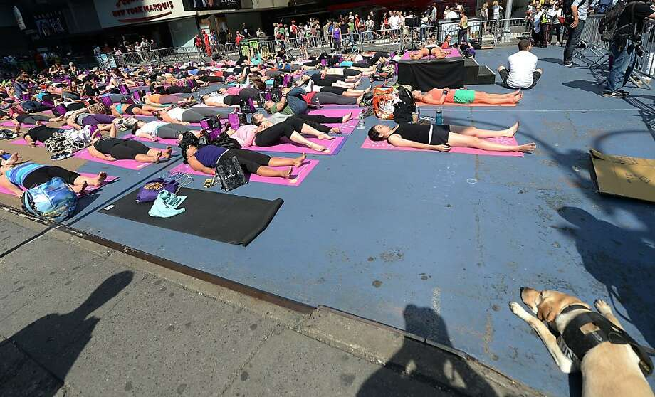 Let a 'downward dog' pro show you how it's done: A police K9 watches New Yorkers practice yoga in Times Square to celebrate the summer solstice. Photo: Emmanuel Dunand, AFP/Getty Images