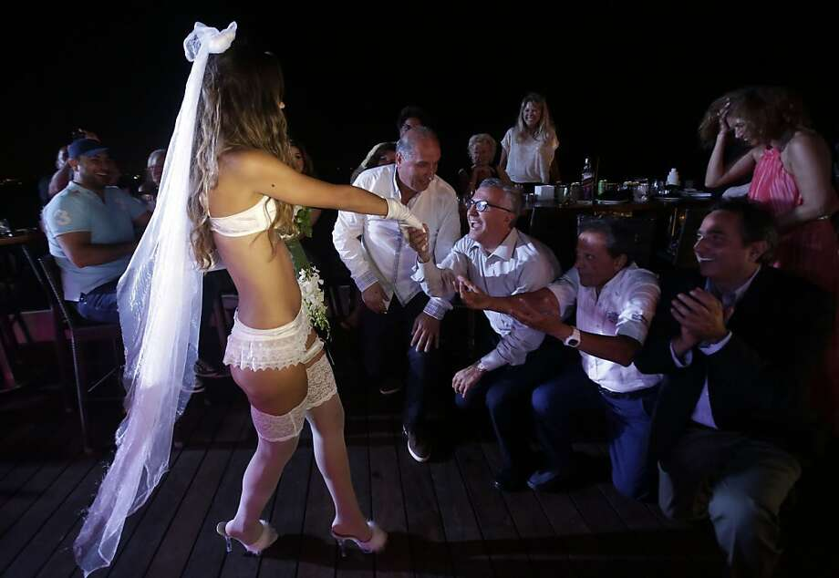 What a lovely bridal gown!Gentlemen at a beach resort in Beirut are eager to meet a model during a lingerie fashion show. Photo: Joseph Eid, AFP/Getty Images