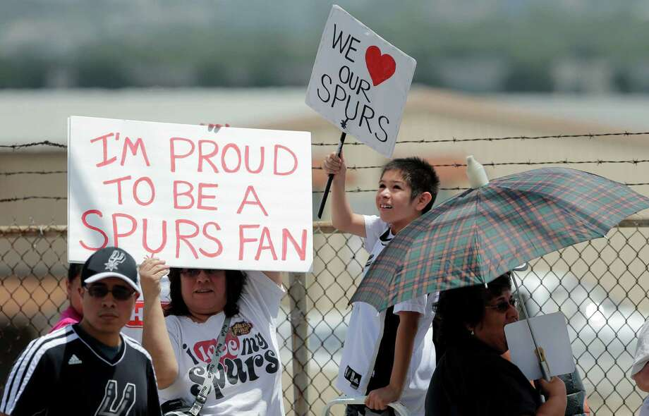 San Antonio Spurs fans stand outside the gates to the airport as they wait for the team to return home after losing to the Miami Heat in the NBA Finals, Friday, June 21, 2013, in San Antonio. (AP Photo/Eric Gay) Photo: Eric Gay, Associated Press / AP