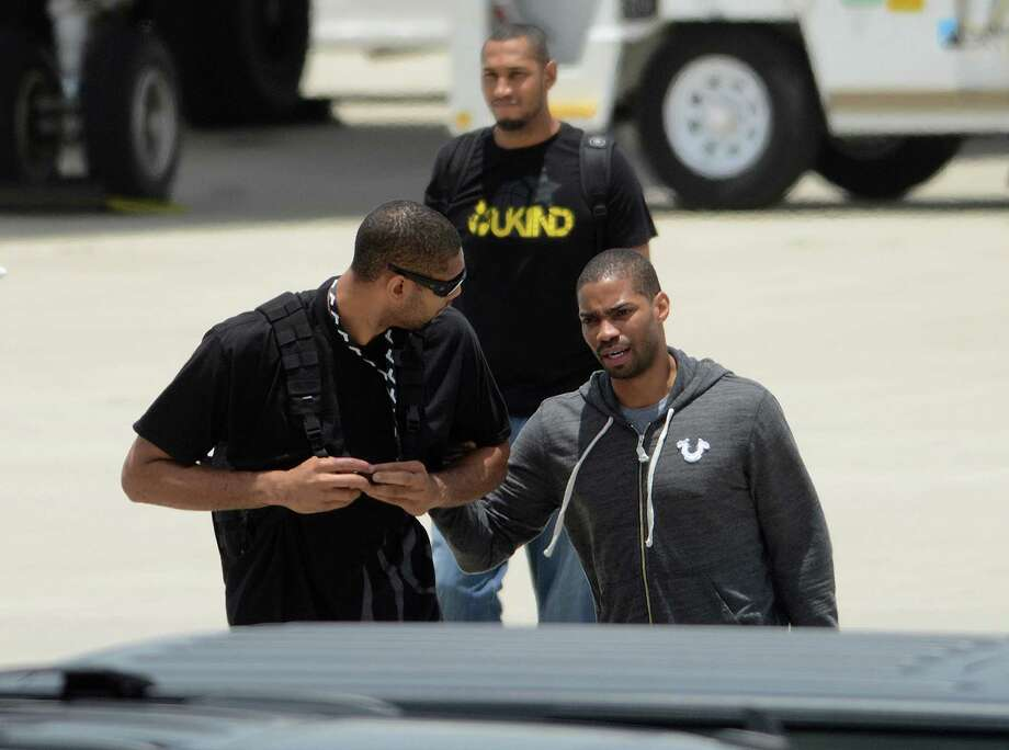 Tim  Duncan, left, and Gary Neal of the San Antonio Spurs speak after arriving at San Antonio International Airport on Friday, June 21, 2013, after representing the NBA's Western Conference in the Championship Series. They lost to the Miami Heat. Teammate Boris Diaw is in background. Photo: Billy Calzada, San Antonio Express-News / San Antonio Express-News