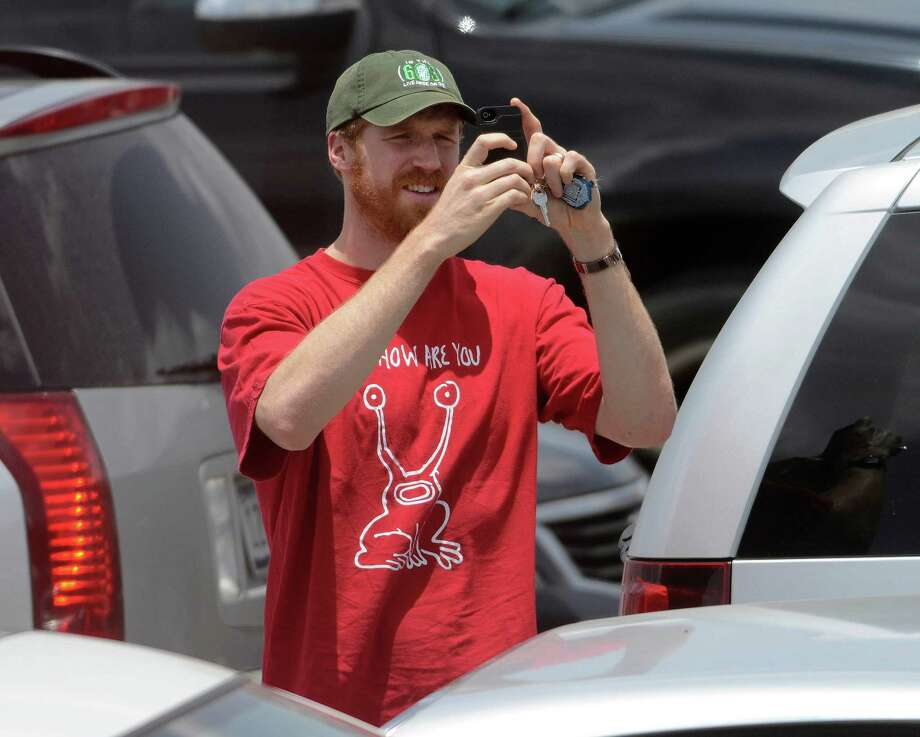 Matt Bonner of the San Antonio Spurs shoots pictures of the welcoming crowd upon arrival at San Antonio International Airport on Friday, June 21, 2013, after representing the NBA's Western Conference in the Championship Series. They lost to the Miami Heat. Photo: Billy Calzada, San Antonio Express-News / San Antonio Express-News