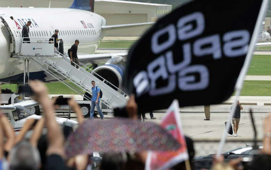 San Antonio Spurs Tiago Splitter walks away from the plane as Gary Neal, left to right on the stairs, Danny Green and Tim Duncan arrive at the San Antonio International Airport to a large fan crowd on Friday, June, 21, 2013. Photo: Bob Owen, San Antonio Express-News / ©2013 San Antonio Express-News