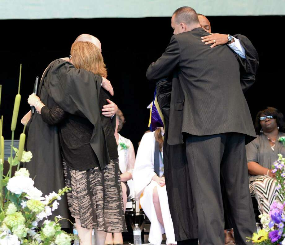 The family of the crash victim Deanna Rivers is warmly greeted by Oliver Robinson, Shenendehowa superintendent, right, and Principal Donald Flynt, left, during the commencement ceremony held at the Saratoga Performing Arts Center June 21, 2013 in Saratoga Springs, N.Y.   (Skip Dickstein/Times Union) Photo: SKIP DICKSTEIN / 10022849A