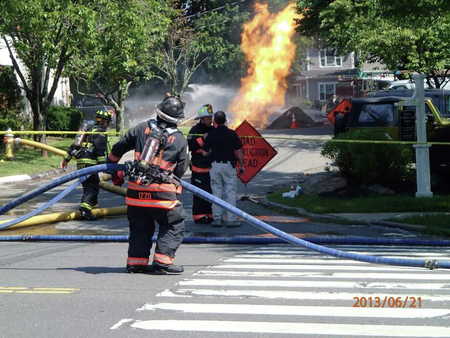 Flames leap from a leaking, underground natural-gas line Friday morning on Westfair Drive, not far off Post Road East. Westport firefighters were able to douse the fire after gas to the line was turned off. Traffic was diverted off of Post Road for more than 90 minutes. Photo: Contributed Photo / Westport News
