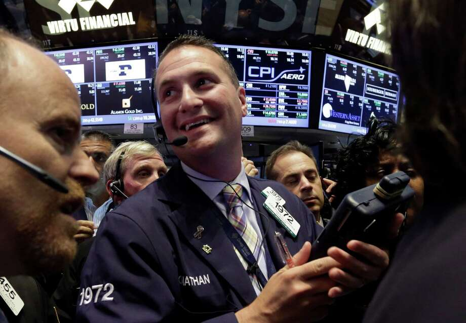 Trader Jonathan Corpina, center, smiles as he works on the floor of the New York Stock Exchange, Friday, June 21, 2013. The stock market is closed out a wild week with a modest gain as the Dow Jones industrial average rose 41 points Friday, or 0.3 percent, to end at 14,799. (AP Photo/Richard Drew) Photo: Richard Drew, Associated Press / Associated Press