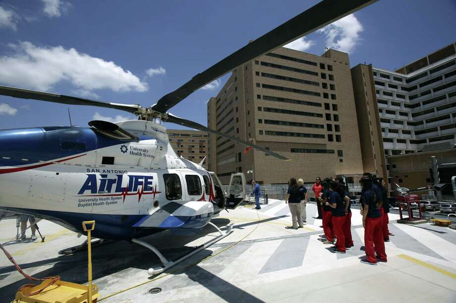 Fox Tech students at Camp 98.6 watch as AirLIFE crew members and their helicopter prepare to take off on an emergency medical call.  During their one-week stint, 10 students from Fox Tech Magnet High School saw lifesaving and medical procedures.. Photo: Photos By Helen L. Montoya / San Antonio Express-News