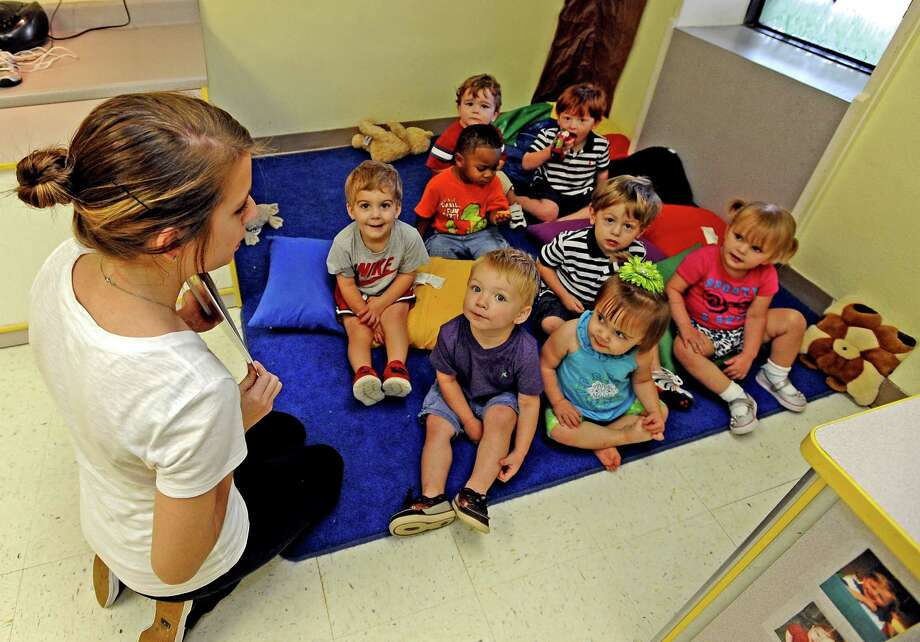 First United Methodist Church child care teacher, Morgan Wheeler, reads a book to the toddlers she looks over in the daycare located in downtown Beaumont on Friday, June, 21, 2013. Photo taken: Randy Edwards/The Enterprise