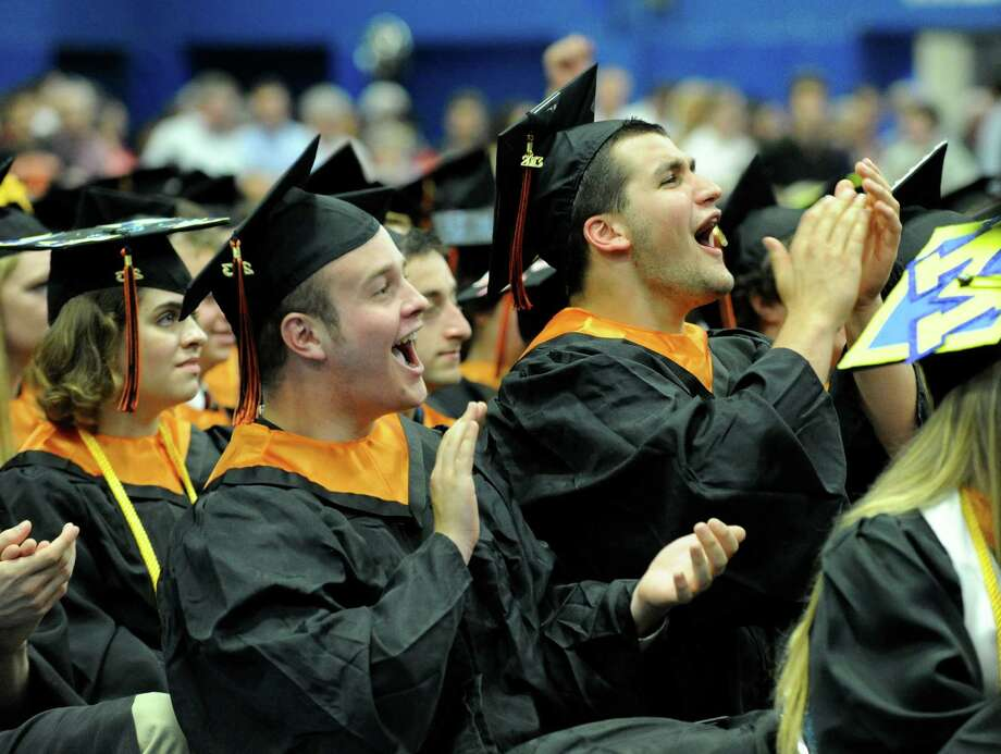 Patrick Barton, left, and Andrew Barton cheer fellow graduates as they receive their diplomas Friday afternoon. Ridgefield High School holds its graduation ceremony Friday, June 21, 2013, at the O'Neill Center at Western Connecticut State University in Danbury, Conn. Photo: Carol Kaliff / The News-Times