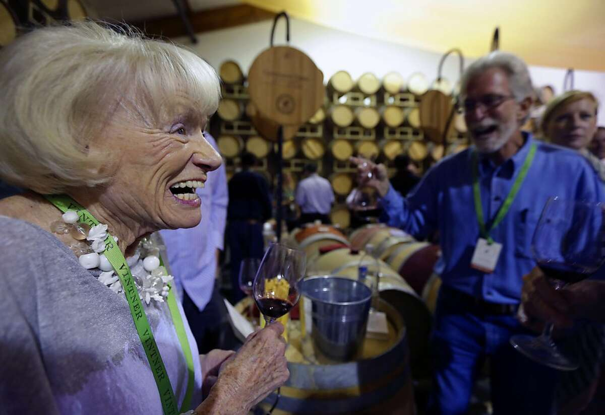 Magrit Mondavi, left, widow of Robert Mondavi, enjoys a barrel sample of Continuum Estate wine made by her stepson Tim Mondavi, right, during the barrel auction event of Auction Napa Valley at Rutherford Vineyards Friday, May 31, 2013 in St. Helena, Calif. Proceeds from the annual weekend event support community health and children's education. The event has given more than $111 million to dozens of these organizations. (AP Photo/Eric Risberg)