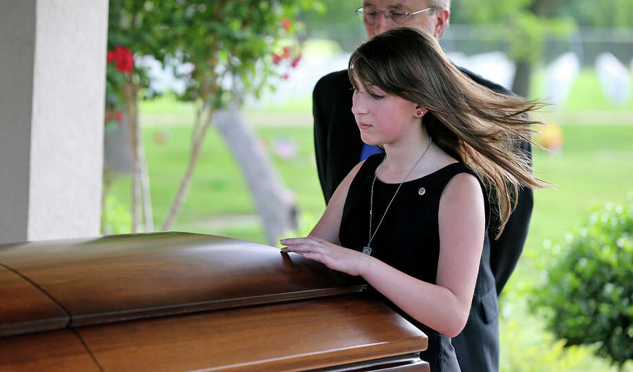 Madison Clark comes forward, with her grandfather Paul Wuenstel and touches the casket of her father as Lt. Col.Todd J. Clark is honored in burial services at Fort Sam Houston National Cemetery on June 21, 2013. Photo: TOM REEL