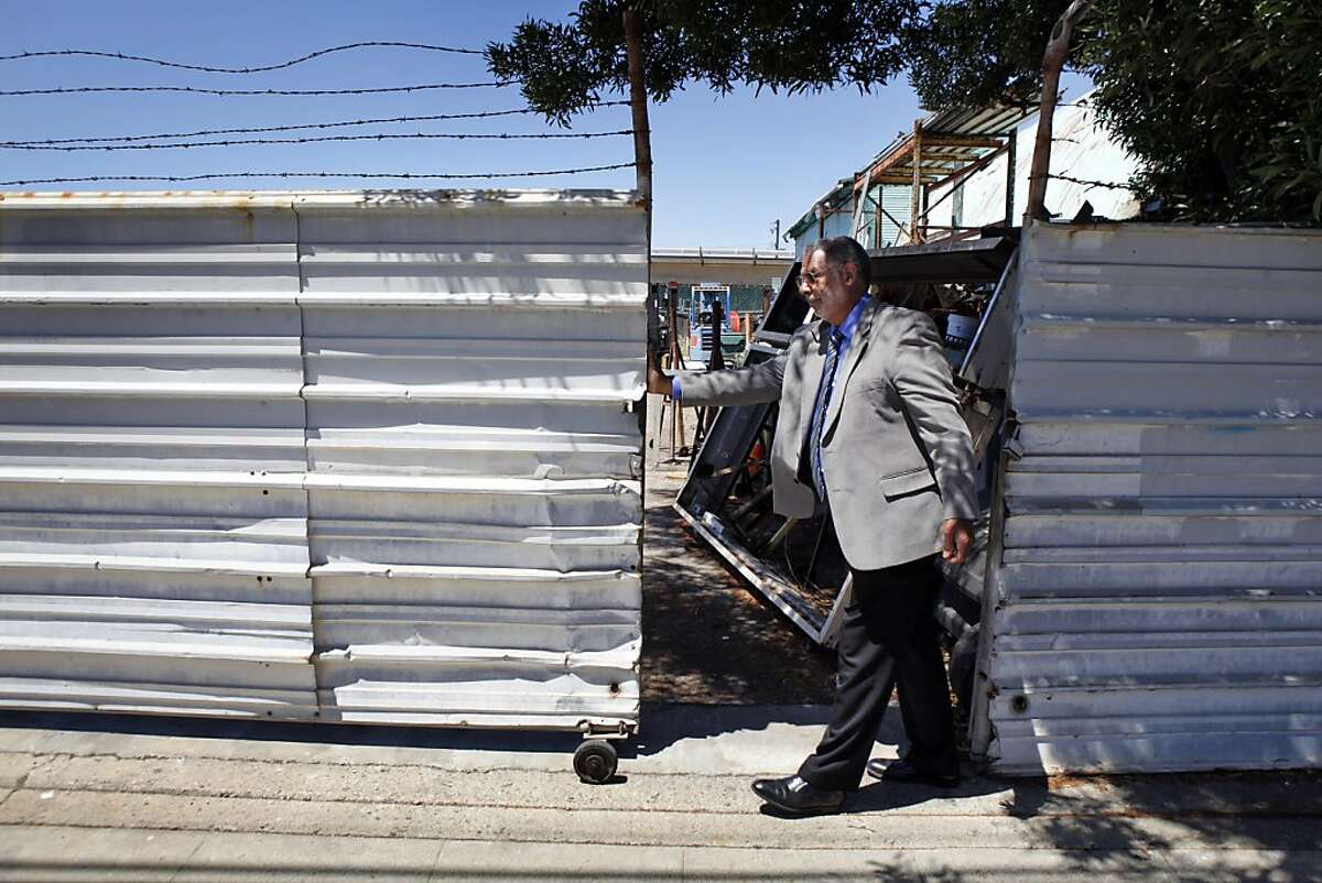 Corky Boozé opens the fence to his commercial property on Wednesday, June 19, 2013, in Richmond, Calif. Boozé is facing a lawsuit by the city council for failing to comply with blight ordinances.