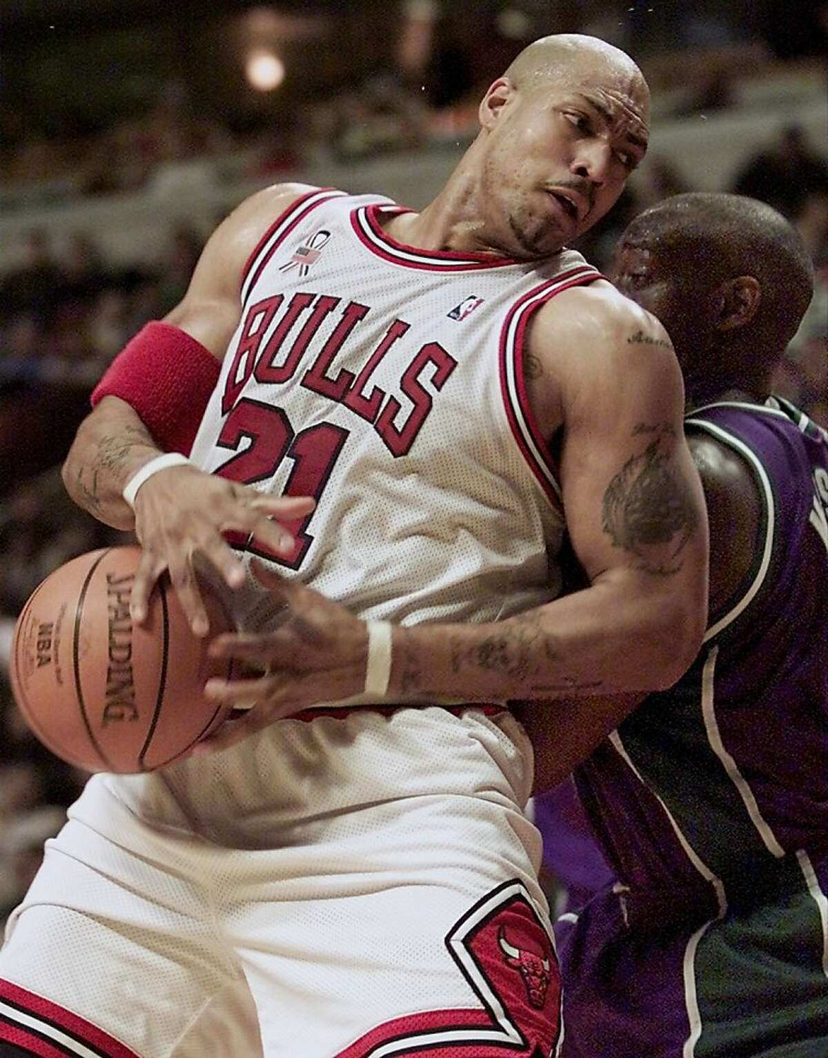Chicago Bulls forward Marcus Fizer (L) is fouled from behind by Milwaukee Bucks forward Anthony Mason (R) in the fourth quarter in Chicago, December 31, 2001. Chicago won the game, 90-83. REUTERS/Sue Ogrocki