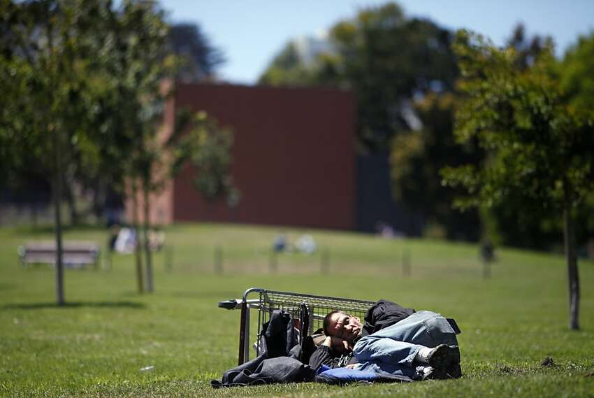 A homeless man sleeps in the sun at Duboce Park in S.F. The biennial homeless count showed 6,436 homeless people this year, about the same as in 2011.