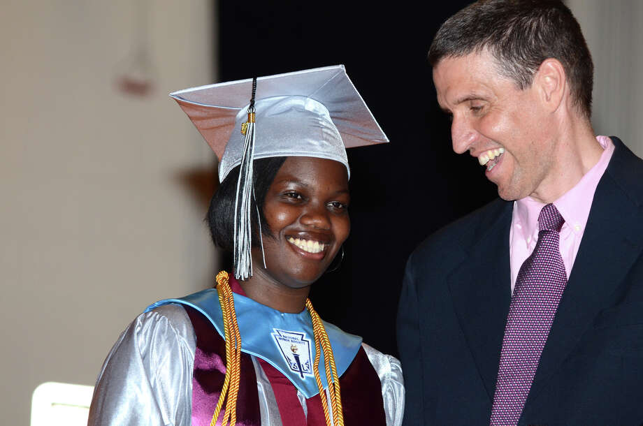 Valedictorian Bryana Spencer smiles after receiving her diploma from Tim Dutton, Director of Bridge Academy, during Bridge Academy's 2013 commencement excercises held at Thurgood Marshall Middle School auditorium in Bridgeport on Friday, June 21, 2013. Photo: Amy Mortensen / Connecticut Post Freelance