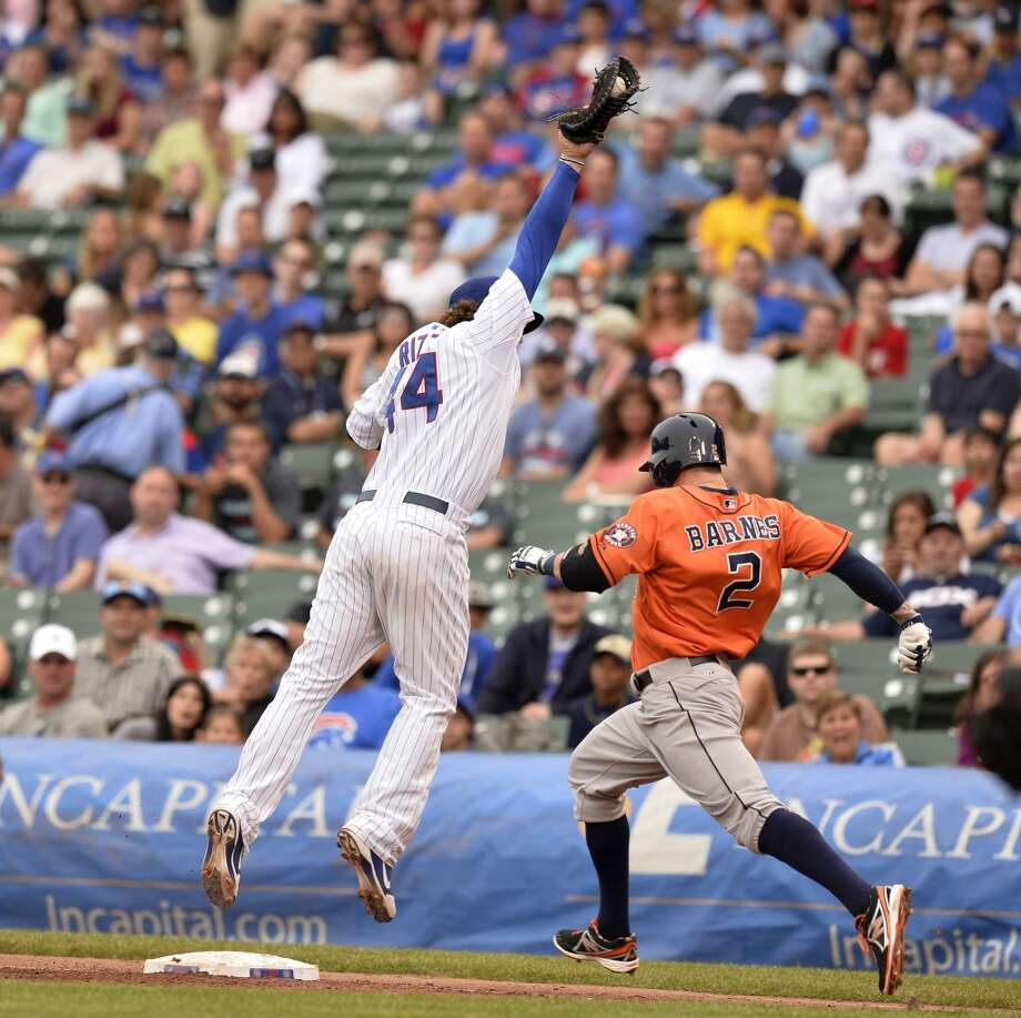 Anthony Rizzo leaps off the bag to catch an errant throw by shortstop Starlin Castro  as Brandon Barnes of the Astros reaches first safely.
