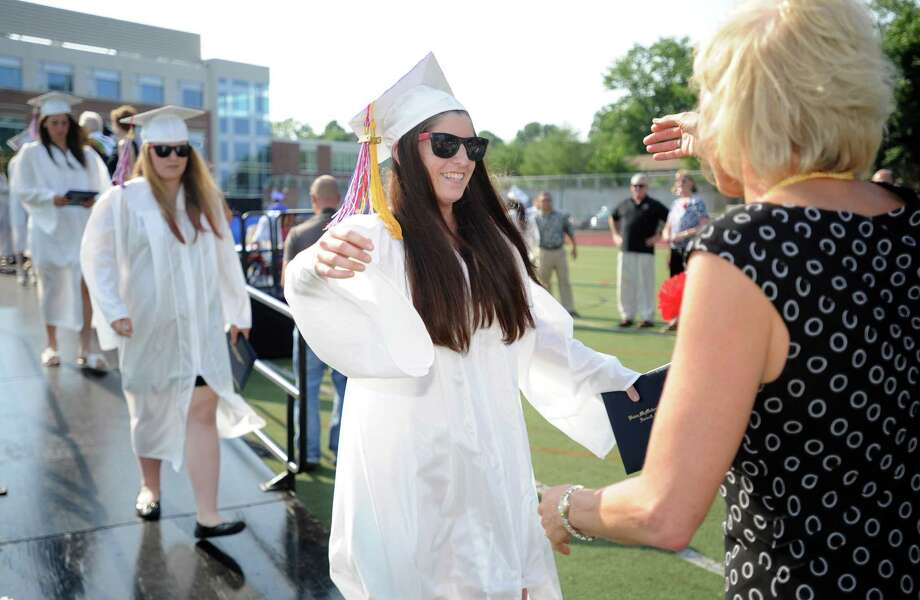 Nicole Angeley gets a hug after getting her diploma during Friday's commencement ceremony at Brien McMahon High School on June 21, 2013. Photo: Lindsay Perry / Stamford Advocate