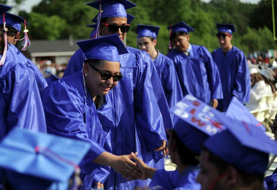 Norberto Lucero gets a handshake on his way to getting his diploma during Friday's commencement ceremony at Brien McMahon High School on June 21, 2013. Photo: Lindsay Perry / Stamford Advocate