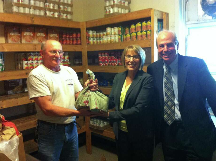 Unity House CEO Chris Burke, right, looks on First Niagara Financial Group Eastern New York Market Leader Nina Tyzik, center, gives a personal donation of canned goods to Mike, of Unity House's food pantry, to complement First Niagara's $5,000 donation to Unity House's 2013 Hunger Appeal. For the past 10 years, First Niagara has provided financial help to support Unity House's programs and services, including its food pantry and Bethany@Unity, a community meals program and resource center that serves breakfast and lunch seven days a week. (Submitted photo)