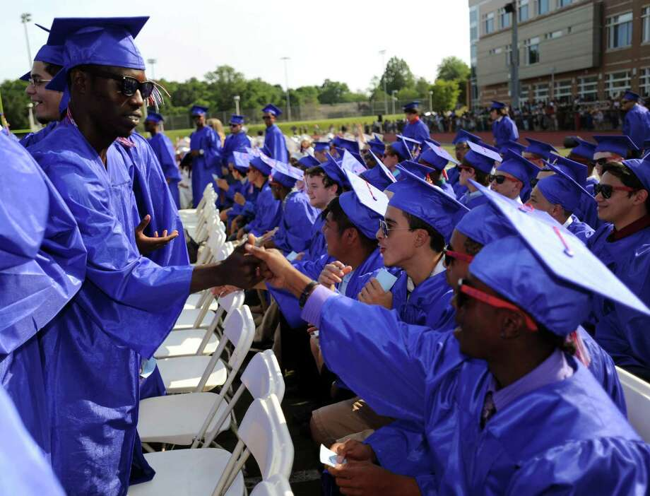 Daniel Morgan gets a high-five during Friday's commencement ceremony at Brien McMahon High School on June 21, 2013. Photo: Lindsay Perry / Stamford Advocate
