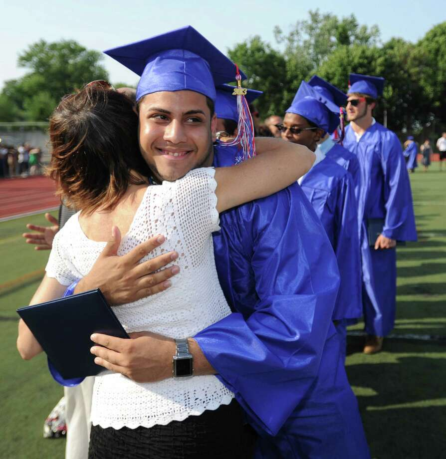 Bryan Martinez gets a hug after getting his diploma during Friday's commencement ceremony at Brien McMahon High School on June 21, 2013. Photo: Lindsay Perry / Stamford Advocate