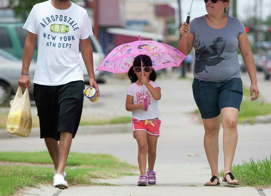 Keeping cool under the cover of her umbrella, Aylin Rodriquez, 4, walks with her mother Griselda, right, and father Osvaldo while walking home from the grocery on the 6100 block of Lyons Ave. Friday, June 21, 2013, in Houston. Photo: Johnny Hanson, Houston Chronicle / © 2013  Houston Chronicle