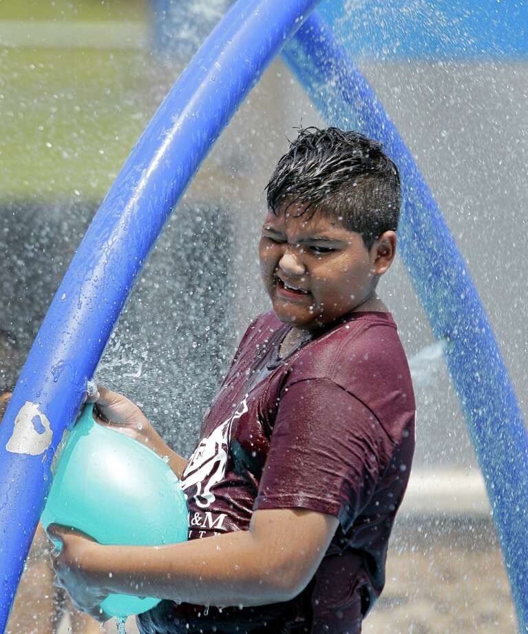 Luis Flores, 11, tries to fill a balloon with water on sprayground at Hidalgo Park, June 21, 2013, in Houston. Photo: Melissa Phillip, Houston Chronicle / © 2013  Houston Chronicle