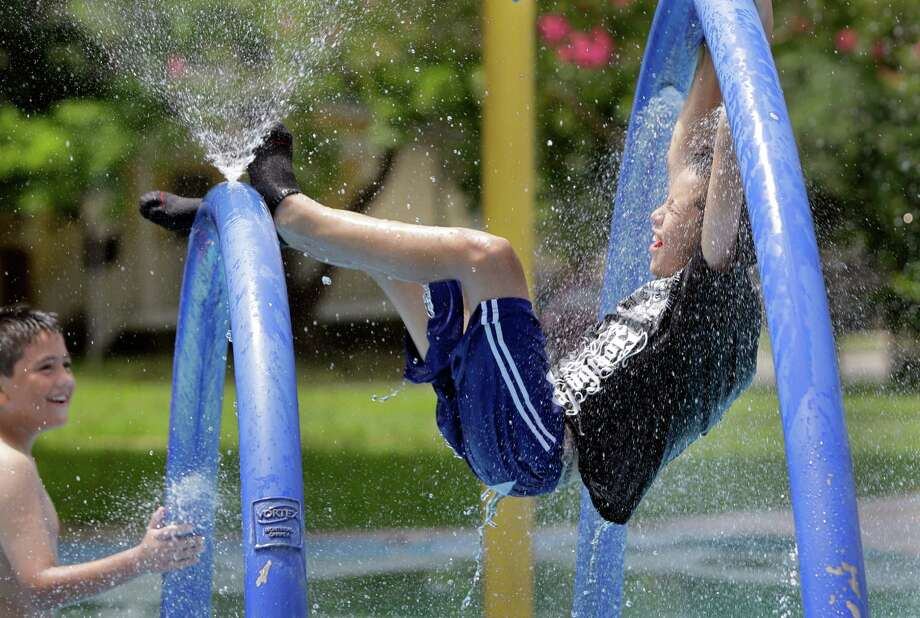 Jonathan Flores, 10, left, and Eduardo Vargas, 11, right, play in sprayground at Hidalgo Park, Friday, June 21, 2013, in Houston. Photo: Melissa Phillip, Houston Chronicle / © 2013  Houston Chronicle