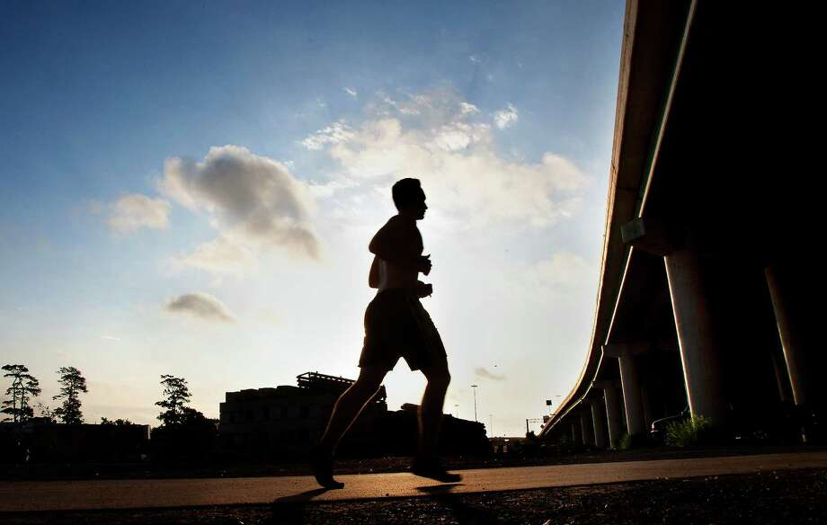 Brian Gillett runs along the paved path near Studewood St., and I-10, Thursday, May 30, 2013, in Houston. Photo: Cody Duty, Houston Chronicle / © 2013 Houston Chronicle