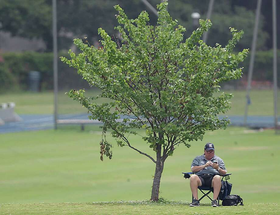 An unidentified man sits under a tree on a hill just outside the field as the University of Houston faces  East Carolina University during the fourth inning of the 2013 Conference USA Championship at Rice University's Reckling Park Thursday, May 23, 2013, in Houston. Photo: James Nielsen, Houston Chronicle / © 2013  Houston Chronicle