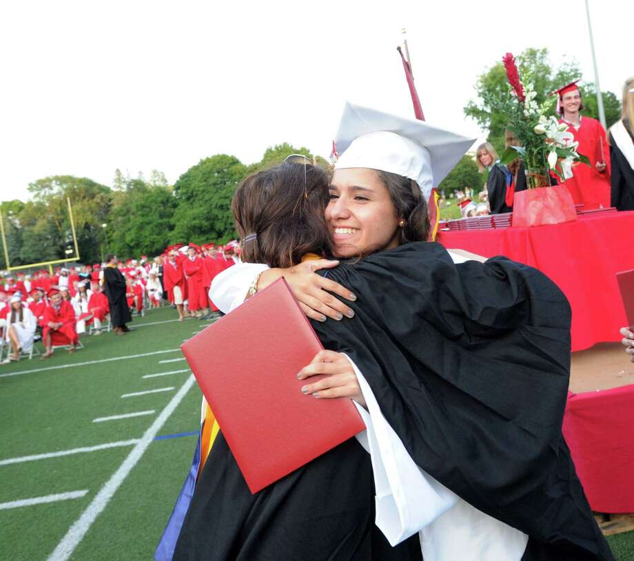 With diploma in hand, Gabriela Franchin, 17, receives a hug during the Greenwich High School graduation ceremony at Cardinal Stadium, Friday evening, June 21, 2013. Franchin said she will be attending the University of Connecticut in the fall. Photo: Bob Luckey / Greenwich Time