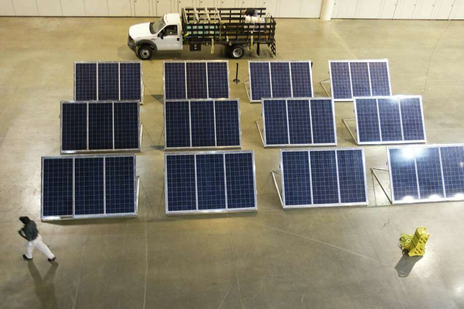 A worker walks past a display of solar panels during a demonstration of a solar-diesel powered disaster relief vehicle and trailer from NRG Energy. The vehicle will deliver power, access to  information and Wi-Fi to those in need. Photo: Brett Coomer / Houston Chronicle