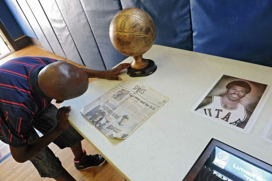 Shalamar Pridget-El, 10, of Albany checks out memorabilia of his uncle and former NBA player Luther (Ticky) Burden, an Albany native, at Trinity Alliance on Friday, June 21, 2013 in Albany, N.Y. (Lori Van Buren / Times Union) Photo: Lori Van Buren / 00022902A
