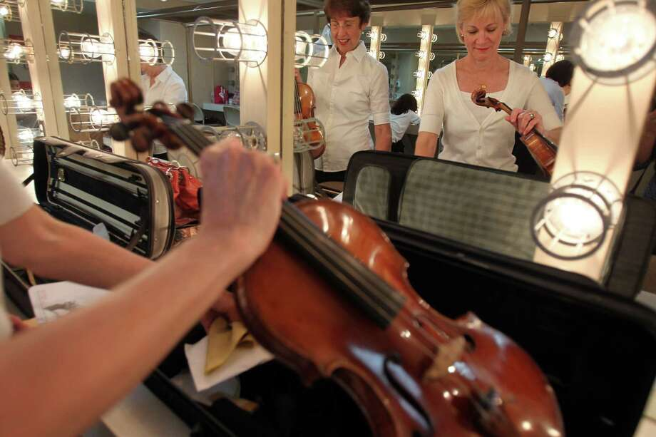 Violinist Christie Pastorek and Martha Chapman touch up makeup and prepare their instruments before the Houston Symphony 100th birthday concert at Miller Outdoor Theater on Friday, June 21, 2013, in Houston. Photo: Mayra Beltran / © 2013 Houston Chronicle