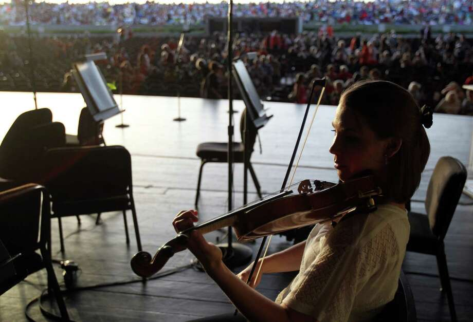 Violinist Emily Kelley warms-up before the Houston Symphony 100th birthday concert at Miller Outdoor Theater on Friday, June 21, 2013, in Houston. Photo: Mayra Beltran / © 2013 Houston Chronicle