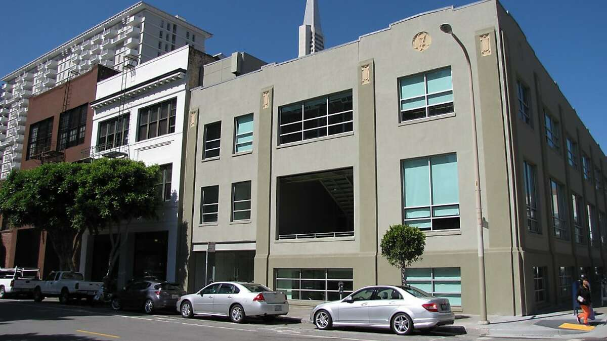 A simple but straightforward industrial building at Front and Pacific streets has added drama because to the cut into the second-floor central bay to create a cave-like open terrace above the street.