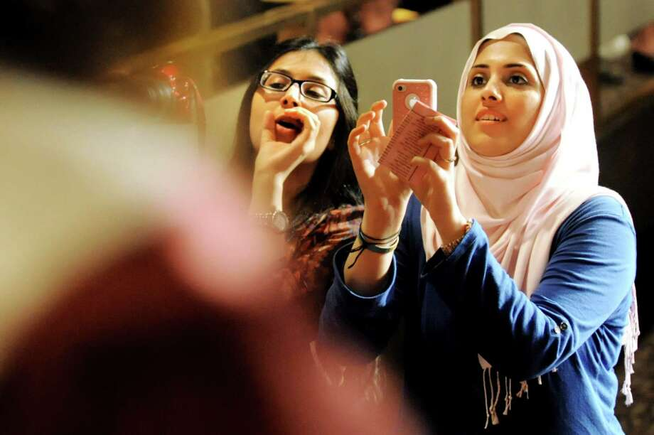 Sisters Fatima Aizaz, left, and Rubab Zahra photograph their brother Mohammad Turaab as graduates file in for the South Colonie High commencement exercises on Friday, June 21, 2013, at the Convention Center in Albany, N.Y. (Cindy Schultz / Times Union) Photo: Cindy Schultz / 10022844A