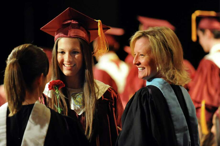 Graduate Mikaela Keegan, center, receives her diploma during the South Colonie High commencement exercises on Friday, June 21, 2013, at the Convention Center in Albany, N.Y. (Cindy Schultz / Times Union) Photo: Cindy Schultz / 10022844A