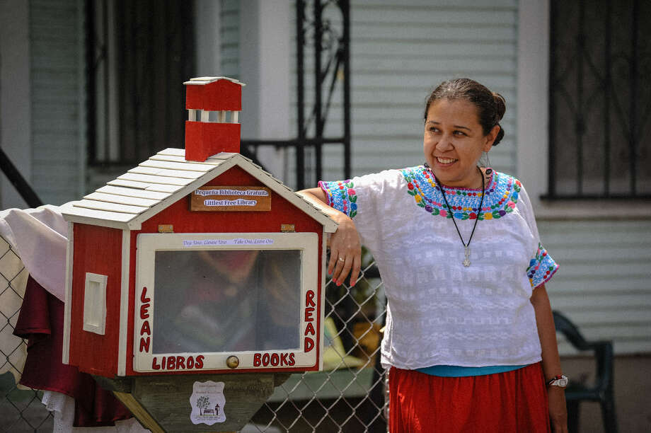 Susana Segura, project development coordinator for the Esperanza Peace and Justice Center, leans against the Little Library during its grand opening ceremonies Friday. Photo: Photos By Robin Jerstad / For The San Antonio Express-News