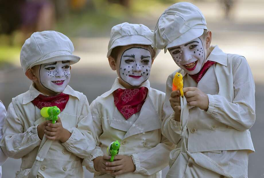 Children wearing vintage outfits prepare to perform during an open air theater show at a park in Bucharest, Romania, Friday, June 21, 2013. The little performers gathered in symbolic costumes to present their theatrical performances to the assembled audience. (AP Photo/Vadim Ghirda) Photo: Vadim Ghirda, Associated Press