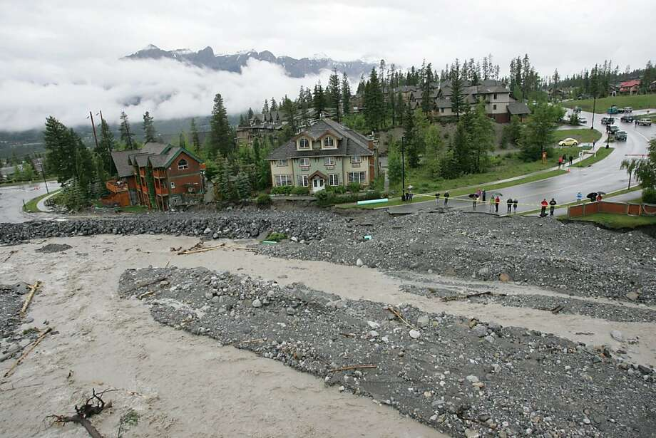 Residents in the Eagle Terrace neighborhood of Canmore, Alberta, look out over what was the only road into the area on Friday June 21, 2013, after Cougar Creek flooded. (AP Photo/The Canadian Press, Rocky Mountain Outlook, Craig Douce) Photo: Craig Douce, Associated Press