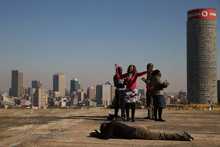 JOHANNESBURG, SOUTH AFRICA - JUNE 21:  Worshipers sing and pray on top of an unfinished building on a hill overlooking downtown in the Yeoville neighborhood June 21, 2013 in Johannesburg, South Africa. The worn, arid space on top of the Yeoville hill offers worshipers of various Christian denominations from South African, Botswana, Zimbabwe, the Democratic Republic of Congo and other African nations an open-air space where they can publicly practice their faith with a scenic view of downtown Johannesburg.  (Photo by Chip Somodevilla/Getty Images) Photo: Chip Somodevilla, Getty Images