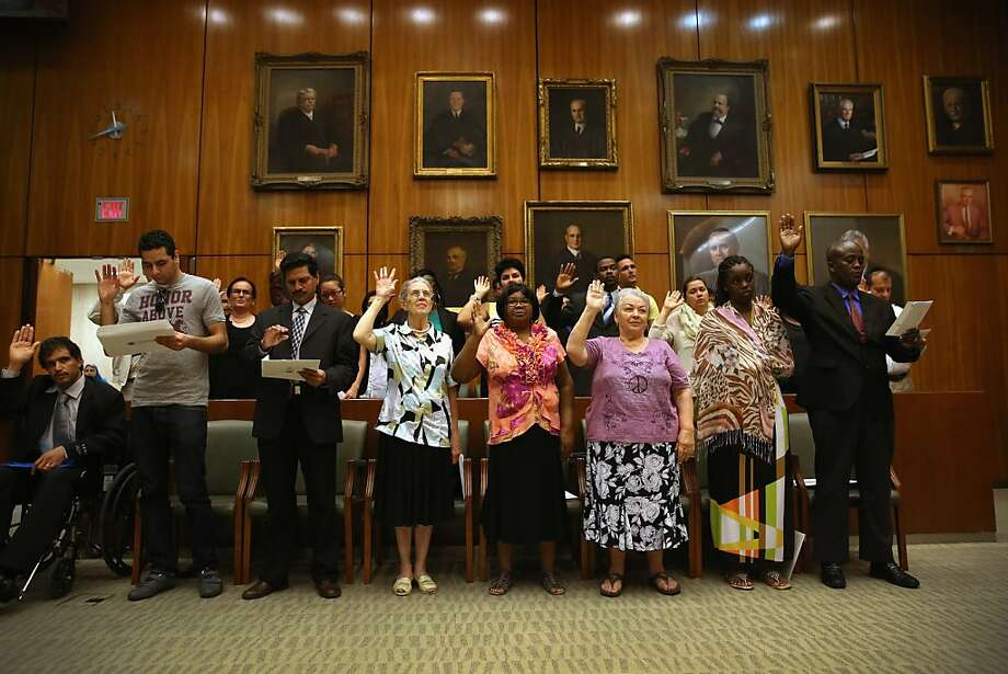 NEW YORK, NY - JUNE 21:  Immigrants become American citizens during a naturalization ceremony under portraits of former federal judges on June 21, 2013 in the Brooklyn borough of New York City. Under the portraits of former federal judges, 270 people took the oath of allegiance during a ceremony held at the Theodore Roosevelt Federal Courthouse in downtown Brooklyn. One of the busiest courthouses for naturalization ceremonies in the nation, the court expects to swear in some 77,000 new American citizens in Brooklyn in 2013.  (Photo by John Moore/Getty Images) Photo: John Moore, Getty Images