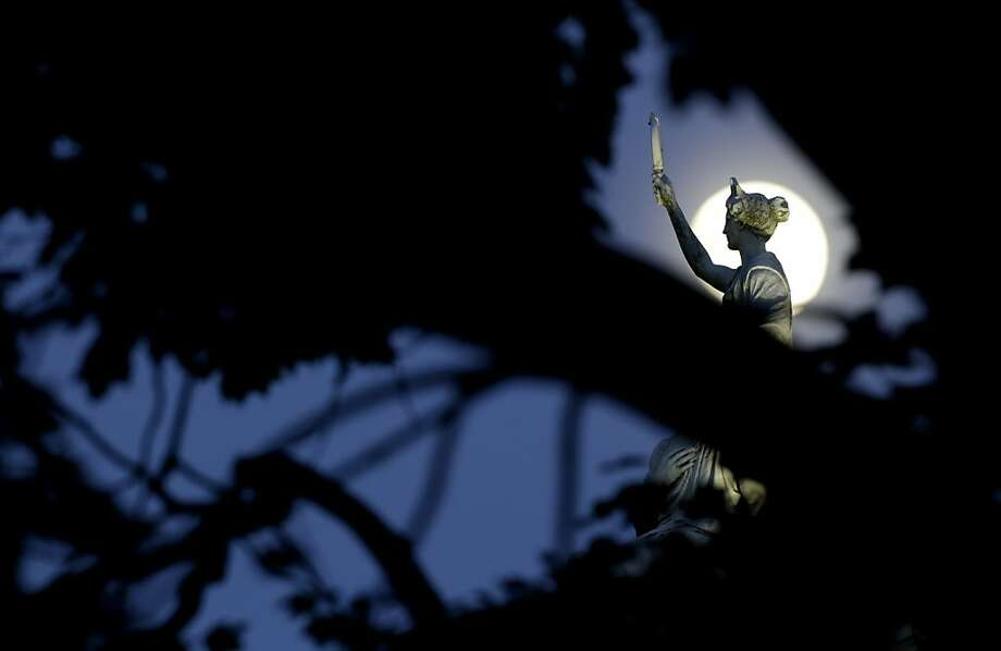 The moon in its waxing gibbous stage sh behind tree limbs and a statue a marble statue by John Gelert representing history and law on the top of the Bergen County Courthouse in Hackensack, N.J., Friday, June 21, 2013. The moon, which will reach its full stage on Sunday, is expected to be 13.5 percent closer to earth during a phenomenon known as supermoon. (AP Photo/Julio Cortez) Photo: Julio Cortez, Associated Press